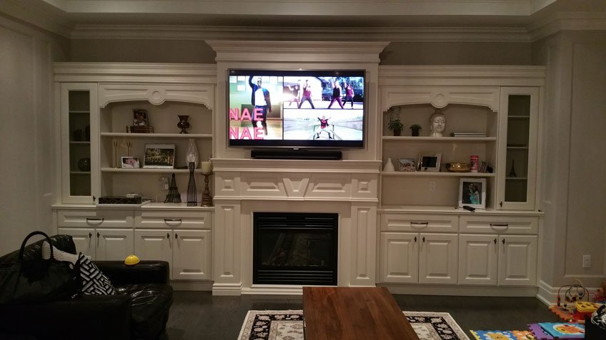 TV & Soundbar installed over fireplace on custom wall unit with components hidden inside the cabinet