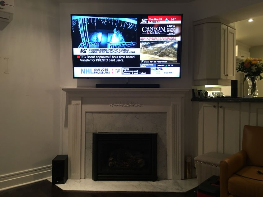 TV & Soundbar installed above fireplace with on-wall wire concealment