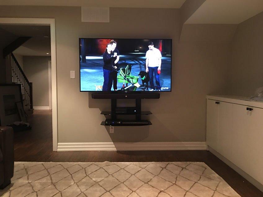 JBL soundbar mounted with universal soundbar brackets between TV and component shelves