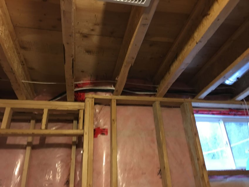 Wires running through the joists across the room in unfinished basement