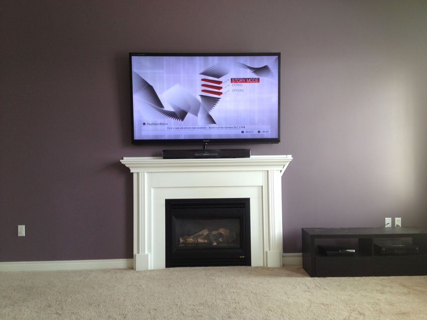 Wires concealed for TV mounted above fireplace using wire raceway cable covers