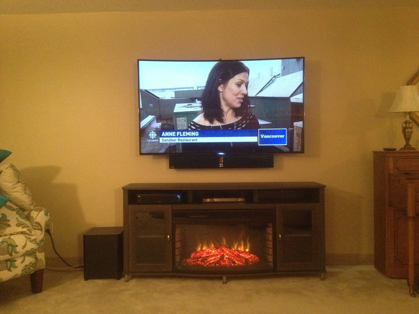 Samsung soundbar mounted below the TV using universal soundbar brackets