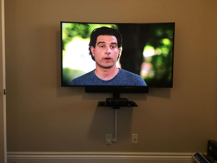 Soundbar mounted between the TV and component wall shelf