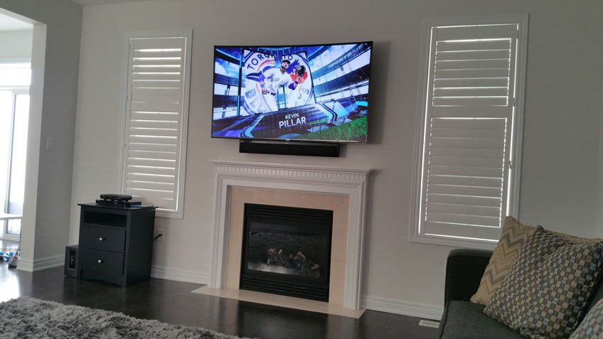 TV installation over fireplace with wires fished through the wall and basement