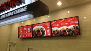 3 commercial display televisions wall mounted side by side to serve as digital menu board
