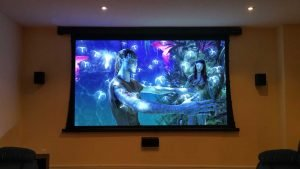 Motorized Tensioned Projector Screen installation between wall mounted satellite speakers