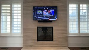 50 inch TV wall mounted with Sonos Beam soundbar attached to it against limestone wall