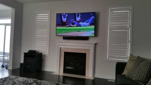 65 inch TV wall mounted with Bose soundbar attached at the bottom over fireplace