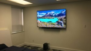 LG soundbar mounted below the wall mounted TV in commercial building