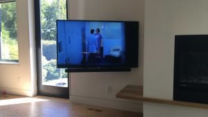 TV wall mounted with soundbar attached to bottom - on swivel mount
