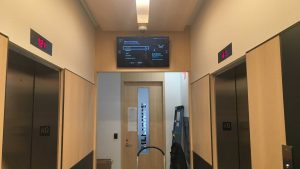 47 inch commercial display TV wall mounted in hallway in condo common area